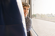 Young man sitting in a train looking through window - FMOF00134