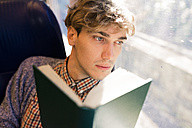 Pensive young man with book sitting in a train looking through window - FMOF00137