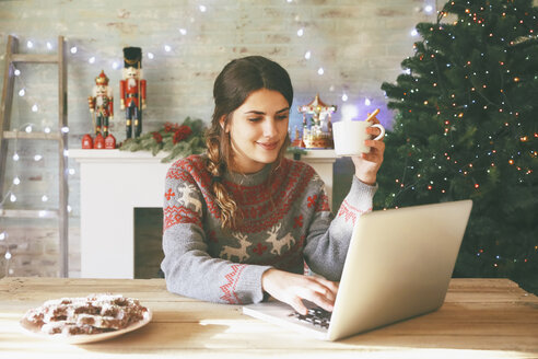 Smiling woman with cup of coffee using laptop at Christmas time - RTBF00429