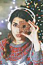Woman with headphones looking through a Christmas cookie - RTBF00432