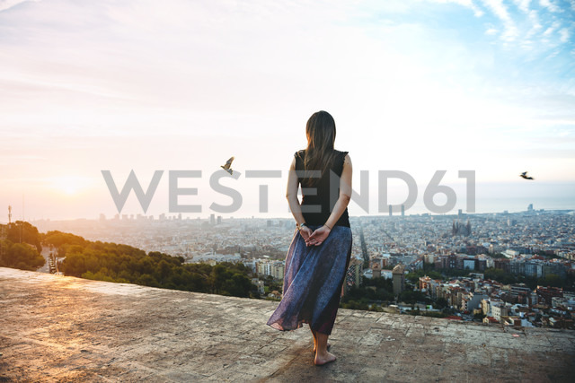 Spain, Barcelona, Woman looking at view over city - GEMF01129