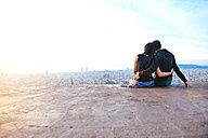 Spain, Barcelona, Embracing couple looking at view over city - GEMF01132