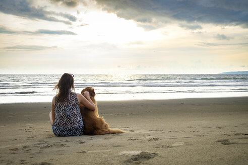 Mexico, Nayarit, Back view of young woman sitting next to her dog at the beach - ABAF02078
