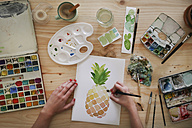 Woman's hand painting aquarelle of a pineapple on desk in her studio - RTBF00434