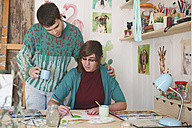 Artist painting in her studio while her boyfriend watching her - RTBF00437