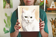 Artist showing aquarelle of a cat - RTBF00443