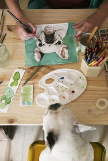 Woman's hand painting an aquarelle of French bulldog - RTBF00446