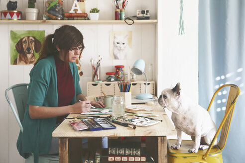 Artist painting an aquarelle of her French bulldog in her studio - RTBF00449