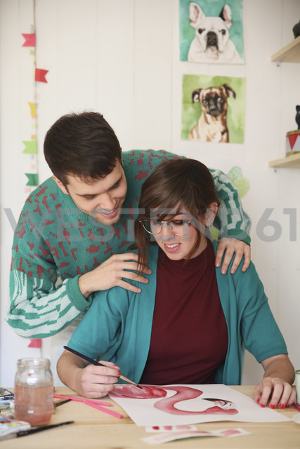 Artist painting an aquarelle while her boyfriend watching - RTBF00455
