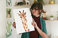 Portrait of artist showing her aquarelle of a giraffe - RTBF00458