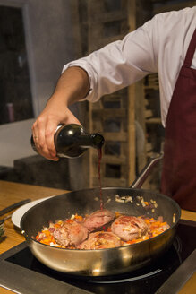 Man pouring wine on beef cheeks in a pan with sauteed vegetables - ABZF01363