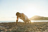 Spain, Mallorca, Jogger at the beach at sunrise, pushups - DIGF01371