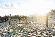 Spain, Mallorca, Jogger at the beach, pushups on rope - DIGF01380