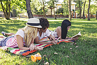Friends in park reading book and using cell phone - DAPF00363