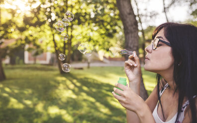 Young woman blowing soap bubbles in park - DAPF00387