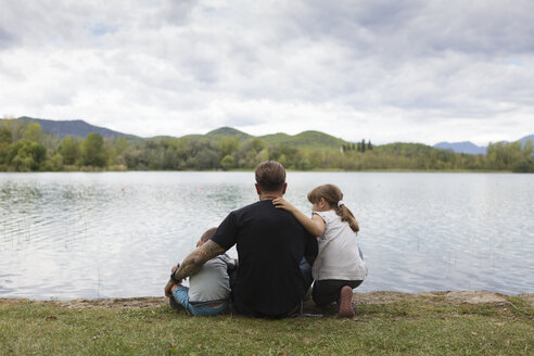 Back view of man sitting with his children at lakeshore - XCF00107