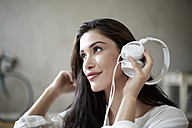 Smiling woman holding white headphones listening music - FMKF03097