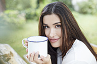 Portrait of smiling woman relaxing with cup of coffee - FMKF03100