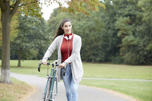 Woman with headphones and bicycle in an autumnal park - FMKF03112