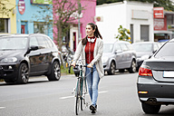 Woman with headphones and bicycle crossing the street - FMKF03115