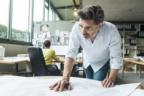 Architect working on ground plan in office - TCF05143