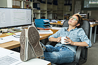 Woman sitting in office with feet up, taking a break - TCF05164
