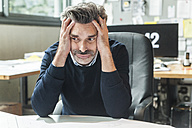 Mature man sitting in office with head in hands - TCF05167