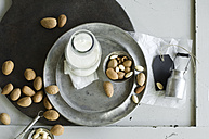 Glass bottle of homemade almond milk and almonds - ASF06026