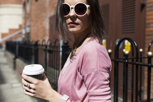 Fashionable young woman with coffee to go wearing pink sunglasses and cardigan - BOYF00591