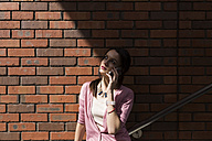 Young woman on the phone in front of brick wall - BOYF00600