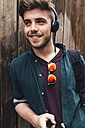 Portrait of happy young man listening music with headphones - BOYF00609