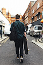 Ireland, Dublin, back view of young man with skateboard walking on the street - BOYF00615