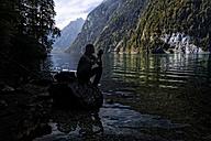 Germany, Bavaria, Woman sitting at Lake Koenigssee - HAMF00222
