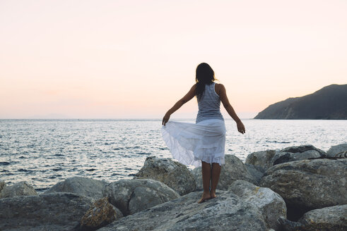 Back view of a woman standing on a rock in front of the sea at sunset - GEMF01140