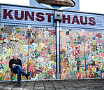 Germany, Burghausen, painter sitting in front of his work at art house - HAMF00233