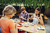 Friends sitting outdoors with coffee and cake taking cell phone pictures - AIF00378