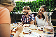 Happy young couple with friend sitting outdoors having coffee and cake - AIF00384