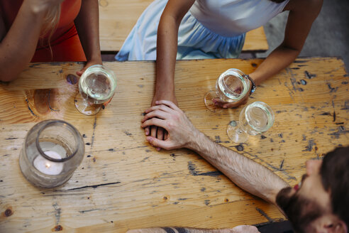 Young couple hand in hand and friend drinking spritzer at outdoor pub - AIF00399