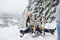 Happy family with sledge in winter landscape - HAPF00951