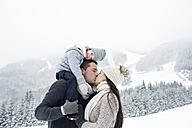 Couple with daughter kissing in winter landscape - HAPF00954