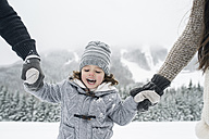 Happy girl hand in hand with parents in winter landscape - HAPF00960