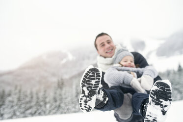 Father holding daughter in winter landscape - HAPF00963