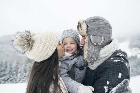 Family in winter landscape with mother kissing daughter - HAPF00966