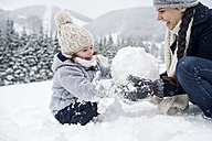 Happy mother with daughter building snowman - HAPF00969