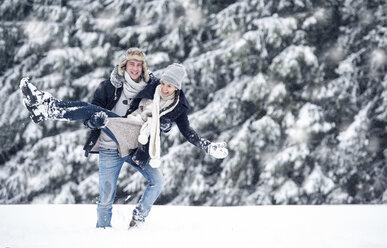 Man carrying girlfriend in winter landscape - HAPF00984
