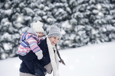 Happy mother carrying daughter piggyback in winter landscape - HAPF00987