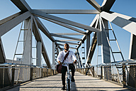 Man riding bicycle on a bridge - JRFF00917