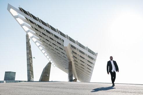 Businessman walking at solar panels - JRFF00923