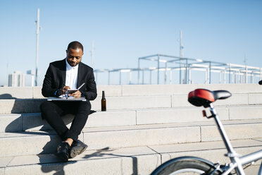 Businessman sitting on stairs with bottle of beer, notebook and laptop - JRFF00929