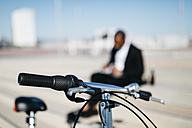 Bicycle handlebar and businessman in background - JRFF00932